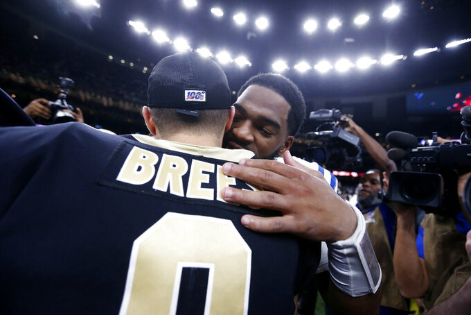 New Orleans Saints quarterback Drew Brees (9) hugs Indianapolis Colts quarterback Jacoby Brissett after defeating the Colts 34-7 in an NFL football game in New Orleans, Monday, Dec. 16, 2019. Brees broke the NFL record for career touchdown passes, surpassing Peyton Manning, and the all-time single game completion percentage as well. (AP Photo/Butch Dill)