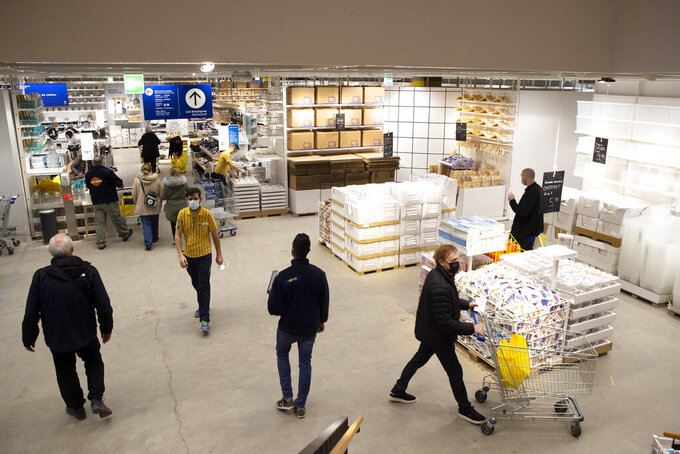 """Customers wearing face masks as a precaution against the spread of coronavirus, in an Ikea store on its reopening day, in Geneva, Switzerland, Monday, March 1, 2021. Swiss authorities last week gave a go-ahead to what they called a """"cautious"""" reopening despite a new, more-transmissible COVID-19 variant that first appeared in Britain that is increasingly circulating in the rich Alpine country. (Salvatore Di Nolfi/Keystone via AP)"""