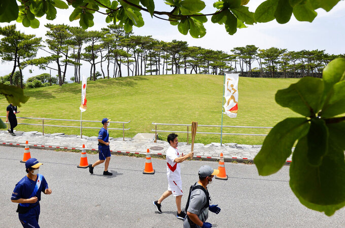 A torch relay runner carries the torch in the Okinawa prefecture's Nago, Japan, Saturday, May 1, 2021. The Tokyo Olympic torch relay will take another detour this weekend when it enters the southern island of Okinawa. A leg of the relay on Okinawa's resort island of Miyakojima set for Sunday has been canceled altogether with cases surging in Japan. Other legs on Okinawa have taken place. (Hiroki Yamauchi/Kyodo News via AP)