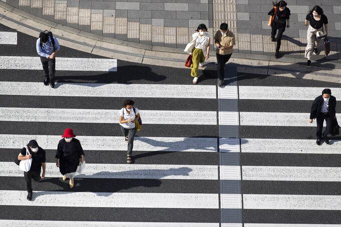 People wearing face masks walk across an intersection in Tokyo on Thursday, July 15, 2021. (AP Photo/Hiro Komae)