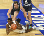 After falling, Air Force's Ameka Akaya tries to pass the ball but puts his foot out of bounds while being defended by Utah State's Justin Bean During the first half of an NCAA college basketball game Thursday, Dec. 31, 2020, at Air Force Academy, Colo. (Jerilee Bennett/The Gazette via AP)