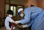 A health worker takes blood sample of a boy during door-to-door testing and screening facility for the coronavirus, Wednesday, June 10, 2020. Pakistan's coronavirus infections soared as the World Health Organization urged the government to impose a two-week lockdown to stem the relentless spike in new cases. (AP Photo/Anjum Naveed)