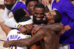 FILE - In this Oct. 11, 2020, file photo, Los Angeles Lakers' LeBron James (23) celebrates with his teammates after the Lakers defeated the Miami Heat 106-93 in Game 6 of basketball's NBA Finals in Lake Buena Vista, Fla. The photo was honored by the Associated Press Sports Editors as best sports feature photo of 2020 at their annual winter meeting. (AP Photo/Mark J. Terrill, File)