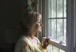 In this Friday, Sept. 13, 2019, photo, Denise Spence poses for a photograph by the window of her home in Palatine, Ill. Spence said her son Timothy died of an opioid overdose. While the nation's attorneys general debate a legal settlement with Purdue Pharma, the opioid epidemic associated with the company's blockbuster painkiller OxyContin rages on. (AP Photo/Teresa Crawfor)