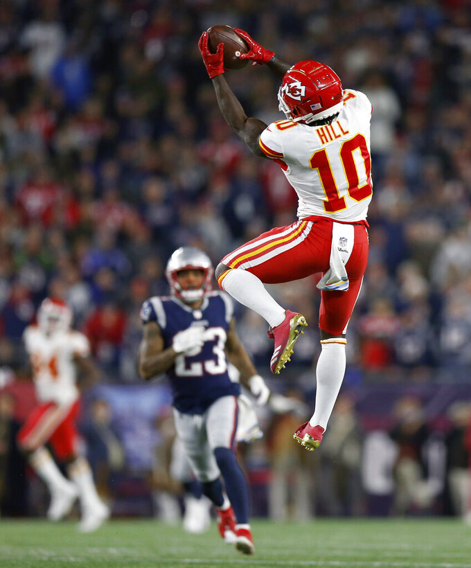 FILE - In this Oct. 14, 2018, file photo, Kansas City Chiefs wide receiver Tyreek Hill (10) catches a pass that he ran in for a touchdown during the second half of an NFL football game against the New England Patriots in Foxborough, Mass. Brady and Mahomes get plenty of attention, but they can't do it alone. Patriots running back James White tied Darren Sproles' postseason record with 15 catches in their 41-28 divisional victory over the Chargers, while Rob Gronkowski and Julian Edelman remain dangerous threats. The Chiefs counter with the pass-catching trio of speedy Tyreek Hill, Sammy Watkins and sure-handed Travis Kelce. (AP Photo/Michael Dwyer, File)