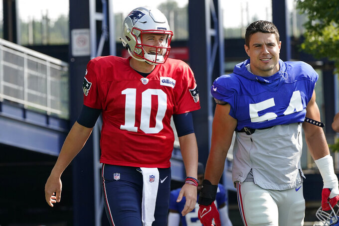 New England Patriots quarterback Mac Jones (10) and New York Giants inside linebacker Blake Martinez (54) step on the field at the start of a joint NFL football practice, Wednesday, Aug. 25, 2021, in Foxborough, Mass. (AP Photo/Steven Senne)