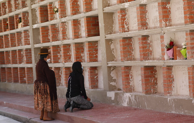 Women pray at the tomb of a relative who died from COVID-19 complications, at the General Cemetery in La Paz, Bolivia, Wednesday, Sept. 23, 2020. (AP Photo/Juan Karita)