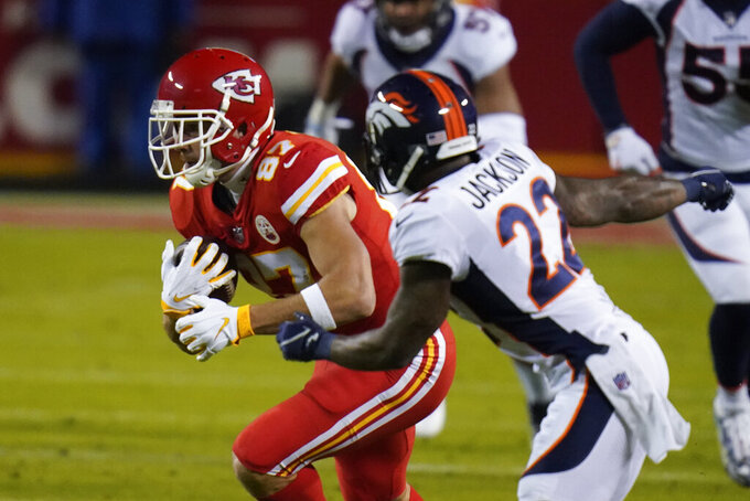 Kansas City Chiefs tight end Travis Kelce (87) runs after a catch as Denver Broncos strong safety Kareem Jackson (22) defends in the first half of an NFL football game in Kansas City, Mo., Sunday, Dec. 6, 2020. (AP Photo/Jeff Roberson)