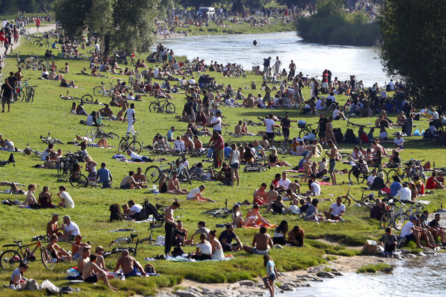 Thousands of people enjoy the summer weather at the 'Isar' river banks in Munich, Germany, Sunday, July 19, 2020. (AP Photo/Matthias Schrader)