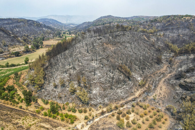 An aerial photo shows destruction by wildfires near the Mediterranean coastal town of Manavgat, Antalya, Turkey, Friday, July 30, 2021. The death toll in a string of wildfires raging in southern Turkey rose to four, officials said Friday, as fire crews continued to battle blazes that burned down homes and forced people to evacuate settlements and beach resorts. Firefighters were still tackling wildfires in 14 locations in six provinces in Turkey's Mediterranean and southern Aegean region, President Recep Tayyip Erdogan told reporters. (AP Photo)