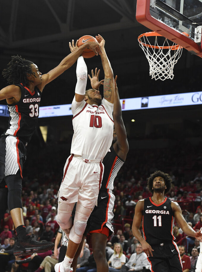 Arkansas forward Daniel Gafford (10) is fouled by Georgia defender Nicolas Claxton (33) as he drives to the hoop during the first half of an NCAA college basketball game, Tuesday, Jan.29, 2019 in Fayetteville, Ark. (AP Photo/Michael Woods)