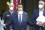 Italian former Premier Silvio Berlusconi is flanked by his personal physician Alberto Zangrillo, right, as he leaves the San Raffaele hospital in Milan, Italy, Monday, Sept. 14, 2020. Berlusconi had been hospitalized as a precaution to monitor his coronavirus infection after testing positive for COVID-19. (AP Photo/Luca Bruno)