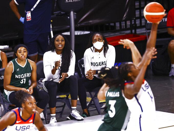 Nigeria guard Erica Erinma Ogwumike (31) watches the action alongside sisters Chiney Ogwumike, center, and Nneka Ogwumike during the first half of a pre-Olympic exhibition basketball game against the United States in Las Vegas on Sunday, July 18, 2021. (Chase Stevens/Las Vegas Review-Journal via AP)