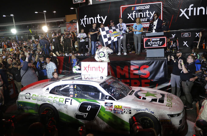 Tyler Reddick waves a checkered flag after winning the NASCAR Xfinity Series championship auto race at the Homestead-Miami Speedway, Saturday, Nov. 17, 2018, in Homestead, Fla. (AP Photo/Lynne Sladky)