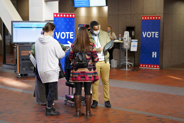 Voters line up to vote at the Hennepin County Government Center, Tuesday, Oct. 27, 2020, in Minneapolis as early voting began for county residents. (AP Photo/Jim Mone)