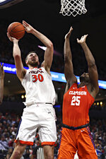 Virginia forward Jay Huff (30) shoots next to Clemson's Aamir Simms during an NCAA college basketball game Wednesday, Feb. 5, 2020, in Charlottesville, Va. (Erin Edgerton/The Daily Progress via AP)