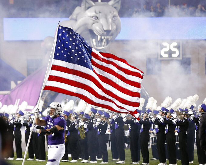 Northwestern's James Prather runs onto the field with a U.S. flag before the start of an NCAA college football game against Notre Dame Saturday, Nov. 3, 2018, in Evanston, Ill. (AP Photo/Jim Young)