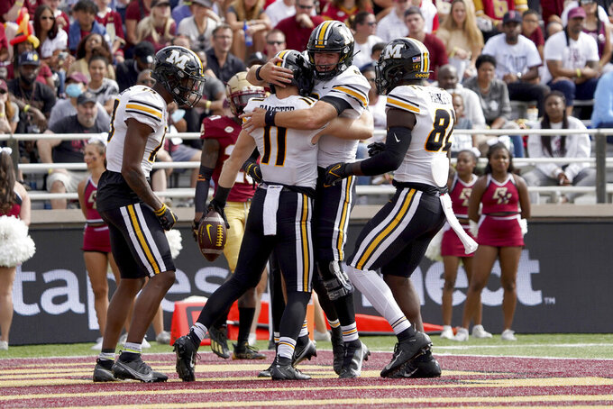 Missouri quarterback Connor Bazelak, facing, congratulates teammate Barrett Banister (11) after Bannister scored a touchdown in the first half of an NCAA college football game against Boston College, Saturday, Sept. 25, 2021, in Boston. (AP Photo/Mary Schwalm)