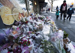 Snow-covered flowers and candles are seen outside of the family bakery of Ayeshe Pourghadheri and her daughter Fatemah Pasavand, who were among the Canadian victims in the Jan. 8 Ukrainian plane crash in Iran, in North Vancouver, British Columbia, Tuesday, Jan. 14, 2020. Iran's judiciary says arrests have been made over the shootdown of the plane that killed all 176 people on board. (Jonathan Hayward/The Canadian Press via AP)