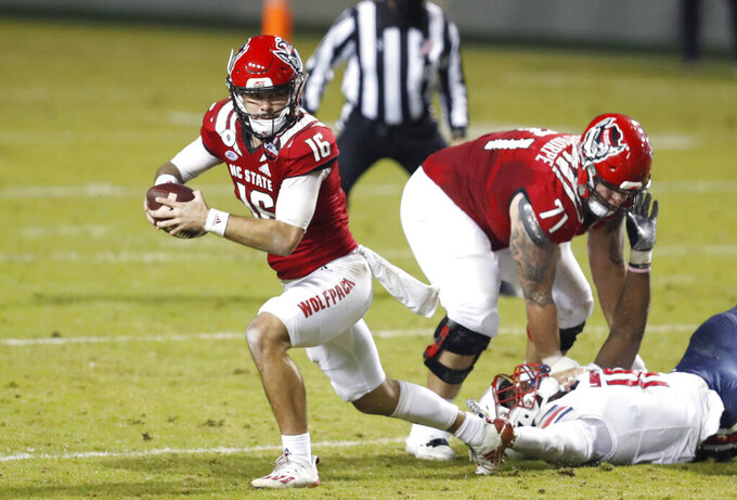 North Carolina State quarterback Bailey Hockman (16) escapes from pressure during the first half of an NCAA college football game against Liberty, Saturday, Nov. 21, 2020, in Raleigh, N.C. (Ethan Hyman/The News & Observer via AP, Pool)