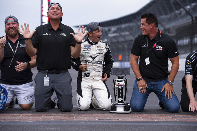 """Kaulig Racing president Chris Rice, second from left, driver AJ Allmendinger, third from left, and team owner Matt Kaulig, right, react while kissing the """"yard of bricks"""" after winning a NASCAR Cup Series auto race at Indianapolis Motor Speedway, Sunday, Aug. 15, 2021, in Indianapolis. (AP Photo/Doug McSchooler)"""