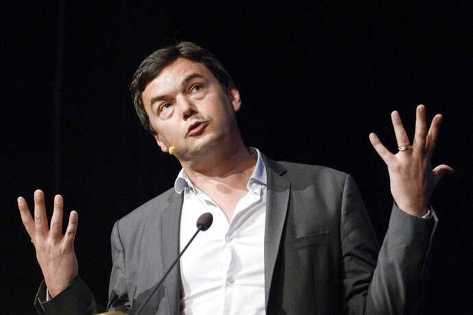 """FILE - In this June 30, 2014 file photo French economist Thomas Piketty speaks during his seminar at the Almedalen political week in Visby on the island of Gotland Sweden. Piketty is out with a new book, a manifesto for political change called """"Capital and Ideology."""" Weighing in at over 1,100 pages, it argues that the level of inequality in a capitalist economy is a direct result of political decisions that can be changed — if governments have the will to do so. (AP Photo/Janerik Henriksson, File)"""