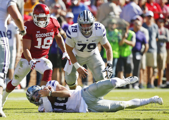 Kansas State quarterback Skylar Thompson (10) recovers his own fumble in front of Oklahoma linebacker Caleb Kelly (19) and teammate Adam Holtorf (79) in the first half of an NCAA college football game in Norman, Okla., Saturday, Oct. 27, 2018. (AP Photo/Sue Ogrocki)