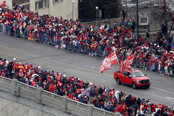 A pickup with Kansas City Chiefs flags travels in a parade through downtown Kansas City, Mo. Wednesday, Feb. 5, 2020 to celebrate the Chiefs victory in NFL's Super Bowl 54. (AP Photo/Charlie Riedel)