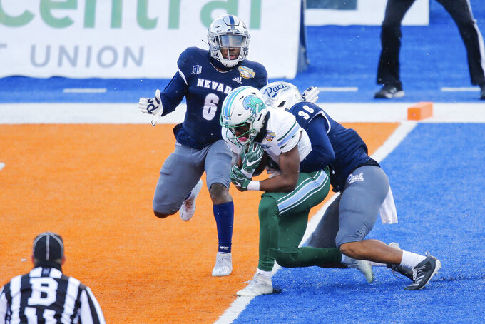 Tulane wide receiver Jha'Quan Jackson (4) drags Nevada defensive back Christian Swint (38) into the end zone for a touchdown during the first half of the Idaho Potato Bowl NCAA college football game, Tuesday, Dec. 22, 2020, in Boise, Idaho. (AP Photo/Steve Conner)