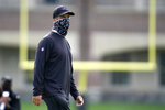 Baltimore Ravens head coach John Harbaugh wears a face mask to protect against COVID-19 as he watches his team warm up during an NFL football camp practice, Monday, Aug. 17, 2020, in Owings Mills, Md. (AP Photo/Julio Cortez)