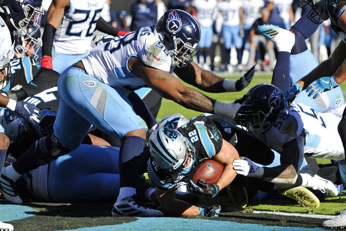 Carolina Panthers running back Christian McCaffrey (22) scores a touchdown while Tennessee Titans defensive tackle Jeffery Simmons (98) can't make the stop during the second half of an NFL football game in Charlotte, N.C., Sunday, Nov. 3, 2019. (AP Photo/Mike McCarn)