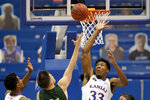 Kansas' David McCormack (33) blocks a shot by North Dakota State's Boden Skunberg (21) during the first half of an NCAA college basketball game Saturday, Dec. 5, 2020, in Lawrence, Kan. (AP Photo/Charlie Riedel)