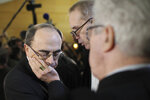 FILE - In this Jan.7, 2019 file photo, Cardinal Philippe Barbarin listens to his lawyers, Jean-Felix Luciani, 2nd right, and Andre Soulier, back to camera, as he attends the start his trial, in Lyon, central France. A French court on Thursday MARCH 7, 2019 is expected to acquit a cardinal and five other defendants accused of protecting a pedophile priest, but alleged victims say France's most important church sex abuse trial has at least allowed them to bring the affair into the open. (AP Photo/Laurent Cipriani, File)