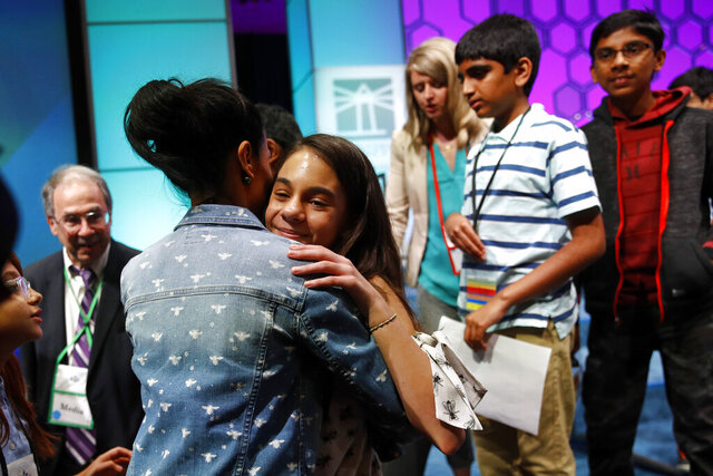 FILE - In this Thursday, May 30, 2019, file photo, Simone Kaplan, of Davie, Fla., hugs her mother, Alana, as she walks offstage after reaching the final round of the Scripps National Spelling Bee, in Oxon Hill, Md. The Scripps National Spelling Bee will have fewer participants in 2020, as organizers are reducing the number of wild-card entrants. (AP Photo/Patrick Semansky, File)