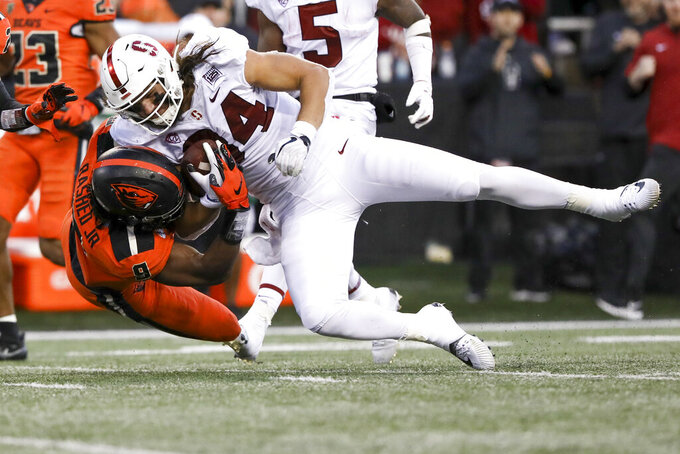 FILE - In this Sept. 28, 2019, file photo, Stanford tight end Colby Parkinson (84) is brought down by Oregon State outside linebacker Hamilcar Rashed Jr. (9) during the second half of an NCAA college football game in Corvallis, Ore. Rashad Jr. was selected to The Associated Press All-America first team, Tuesday, Aug. 25, 2020. (AP Photo/Amanda Loman, File)