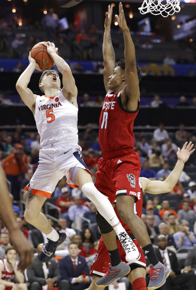 Virginia's Kyle Guy (5) shoots against North Carolina State's C.J. Bryce (13) during the first half of an NCAA college basketball game in the Atlantic Coast Conference tournament in Charlotte, N.C., Thursday, March 14, 2019. (AP Photo/Chuck Burton)