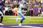 Detroit Lions running back D'Andre Swift (32) scores on a 7-yard touchdown run during the second half of an NFL football game against the Minnesota Vikings, Sunday, Oct. 10, 2021, in Minneapolis. (AP Photo/Bruce Kluckhohn)
