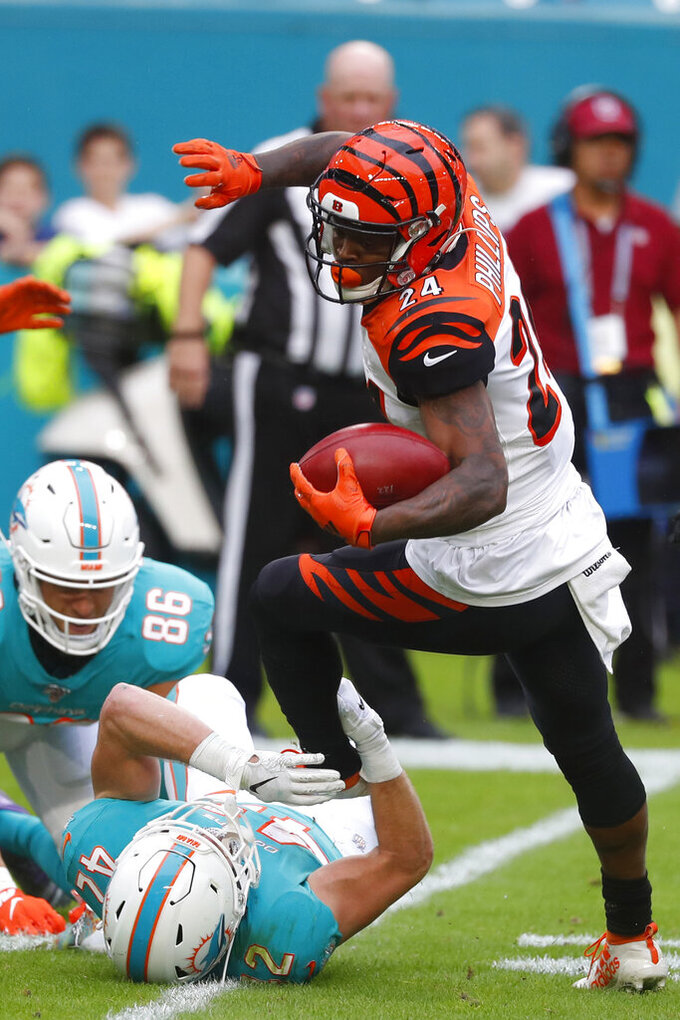 Miami Dolphins running back Patrick Laird (42) grabs Cincinnati Bengals cornerback Darius Phillips (24), during the first half at an NFL football game, Sunday, Dec. 22, 2019, in Miami Gardens, Fla. (AP Photo/Wilfredo Lee)