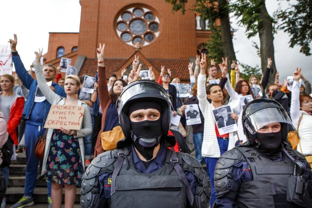 Riot police block protesters in front of a Catholic church in Minsk, Belarus, Thursday, Aug. 27, 2020. Police in Belarus have dispersed protesters who gathered on the capital's central square, detaining dozens. (AP Photo/Dasha Sapranetskaya )