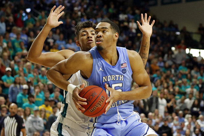 North Carolina's Garrison Brooks (15) battles for the ball with UNC Wilmington's John Bowen (32) during the first half of an NCAA college basketball game in Wilmington, N.C., Friday, Nov. 8, 2019. (AP Photo/Karl B DeBlaker)
