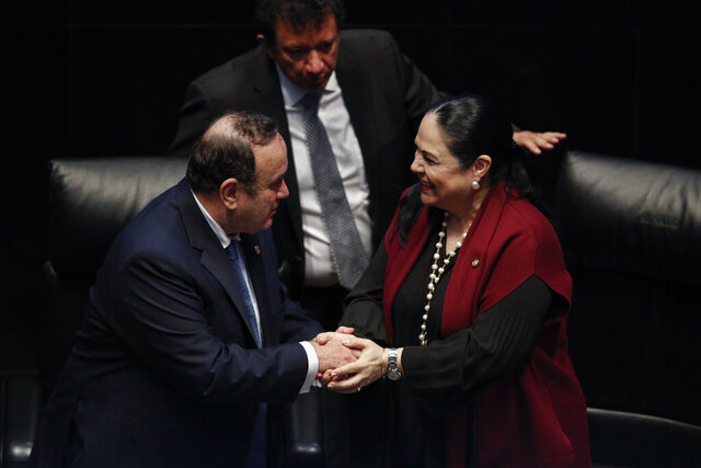 Guatemala's President Alejandro Giammattei shakes hands with Mexican Senate President Monica Fernandez Balboa after addressing the senate members in Mexico City, Thursday, Feb. 6, 2020. (AP Photo/Rebecca Blackwell)