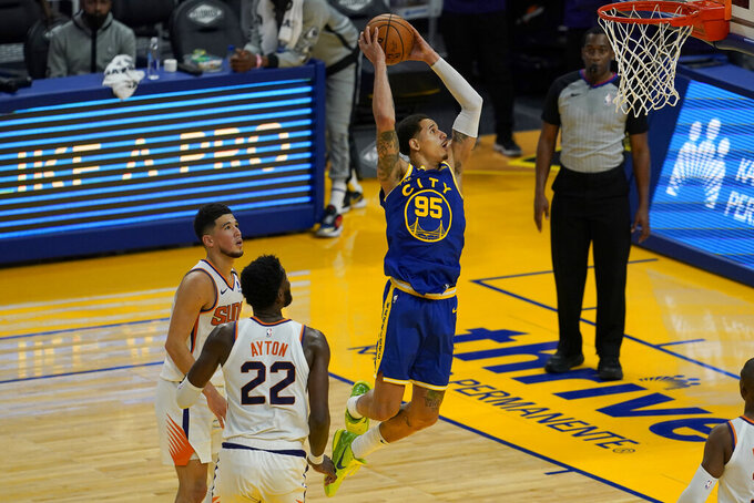 Golden State Warriors forward Juan Toscano-Anderson (95) dunks in front of Phoenix Suns center Deandre Ayton (22) and guard Devin Booker during the first half of an NBA basketball game in San Francisco, Tuesday, May 11, 2021. (AP Photo/Jeff Chiu)