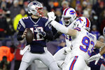 FILE - In this Dec. 21, 2019, file photo, New England Patriots quarterback Tom Brady, left, passes under pressure from Buffalo Bills defensive end Trent Murphy (93) during the first half of an NFL football game in Foxborough, Mass. Between them, Brady and Drew Brees have played 38 pro football seasons, 39 if you count 2008 when the New England star wrecked his knee in Week 1,  and could be doing so against each other on Feb. 2 in a little thing called the Super Bowl. (AP Photo/Elise Amendola, File)
