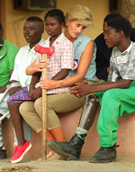 FILE - In this Tuesday Jan. 14, 1997 file photo, Diana, Princess of Wales, talks to amputees, at the Neves Bendinha Orthopedic Workshop near Luanda, Angola during a visit in an effort to create awareness about land-mines. Her son Prince Harry will walk in the footsteps of his mother, whose steps across a mine field in 1997 helped to inspire an international ban on anti-personnel mines. (AP Photo/Joao Silva, File)