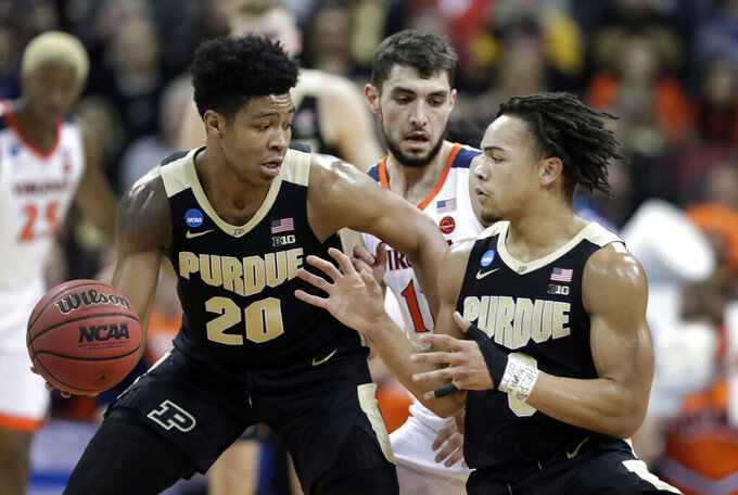 Purdue's Carsen Edwards, right, takes the basketball from teammate Nojel Eastern (20) while being defended by Virginia's Ty Jerome, center, during the first half of the men's NCAA Tournament college basketball South Regional final game, Saturday, March 30, 2019, in Louisville, Ky. (AP Photo/Michael Conroy)