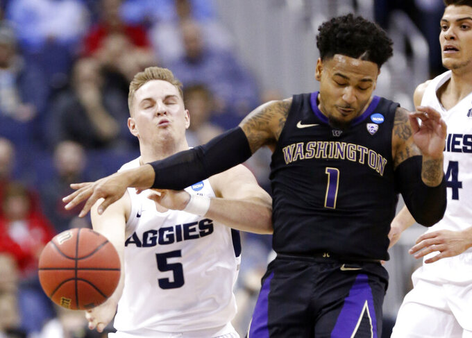 Washington's David Crisp (1) and Utah State's Sam Merrill (5) battle for the ball in the first half during a first round men's college basketball game in the NCAA Tournament in Columbus, Ohio, Friday, March 22, 2019. (AP Photo/Paul Vernon)