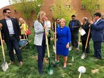 FILE - In this Monday, April 22, 2019 file photo, Gov. Michelle Lujan Grisham, center right, and PNM Resources CEO Pat Vincent-Collawn, center left, celebrate after planting a tree for Earth Day in Albuquerque, N.M. The two leaders gathered with dozens of other state, tribal and local officials to announce that PNM, New Mexico's largest electric provider, was setting a goal to be emissions-free by 2040. (AP Photo/Susan Montoya Bryan)