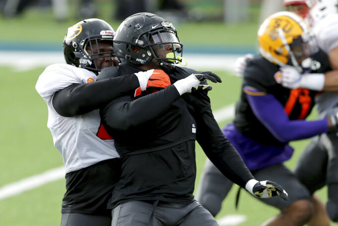 Wake Forest defensive lineman Carlos Basham Jr. is held by Grambling State offensive lineman David Moore, left, during American Team practice Wednesday, Jan. 27, 2021, in Mobile, Ala., for the Senior Bowl college football game. (AP Photo/Rusty Costanza)