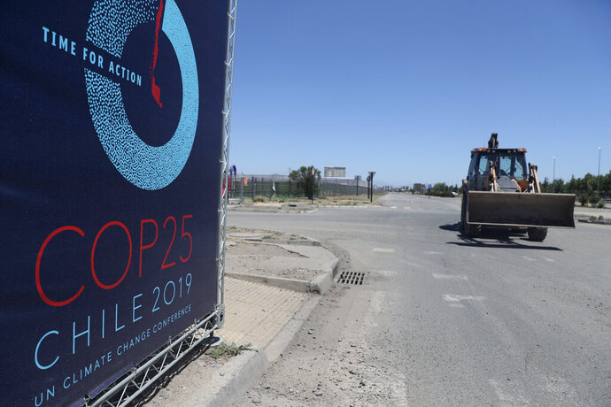 A backhoe drives at the site that was going to be the venue for the COP25 UN climate summit at the Cerrillos Bicentennial Park in Santiago, Chile, Wednesday, Oct. 30, 2019. Chilean President Sebastián Pinera cancelled the COP25 and the APEC summits after nearly two weeks of nationwide protests over economic inequality that have left at least 20 dead and damaged businesses and infrastructure around the country. (AP Photo/Esteban Felix)