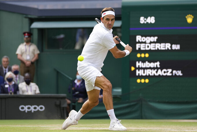 """FILE - In this July 7, 2021, file photo, Switzerland's Roger Federer plays a return to Poland's Hubert Hurkacz during the men's singles quarterfinals match on the ninth day of the Wimbledon Tennis Championships in London. Federer is going to miss the U.S. Open and be sidelined for what he said will be """"many months"""" because he needs a third operation on his right knee. Federer announced the news Sunday, Aug. 15, 2021, via a video message on Instagram. He said he wil be """"out of the game for many months."""" (AP Photo/Kirsty Wigglesworth, File)"""